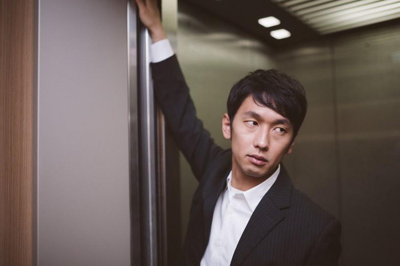 エレベータのドアを押さえる営業