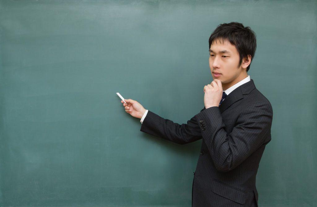 黒板に向かって考え込む先生